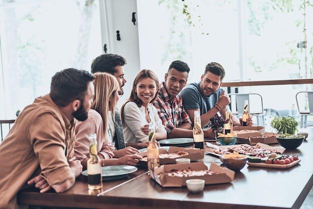 Goede vrienden. groep jongeren in vrijetijdskleding die communiceren en glimlachen tijdens een etentje