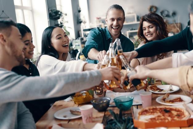 Goede vrienden. groep jongeren in vrijetijdskleding die elkaar roosteren en glimlachen terwijl ze binnen een etentje hebben