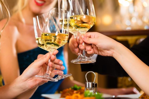 Goede vrienden voor diner of lunch in een goed restaurant, rammelende glazen