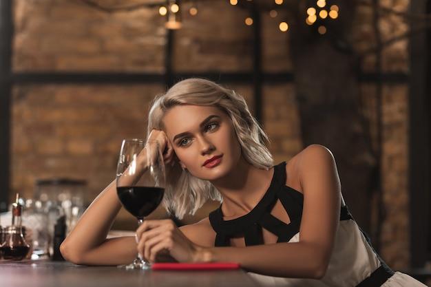 Goede wijn. mooie jonge blonde vrouw zit aan de toog en kijkt naar haar glas wijn terwijl ze aan iets denkt
