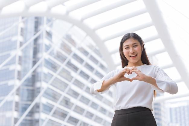 Goede zakelijke service van hart liefde zorg hulp en ondersteuning klant werkconcept. gelukkig vrouwenpersoneel toont hand hartvorm en glimlach.