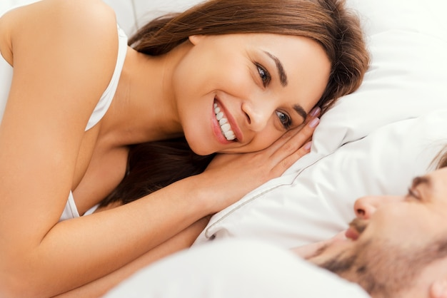 Goedemorgen! bovenaanzicht van mooie jonge verliefde paar in bed liggen en kijken naar elkaar met een glimlach