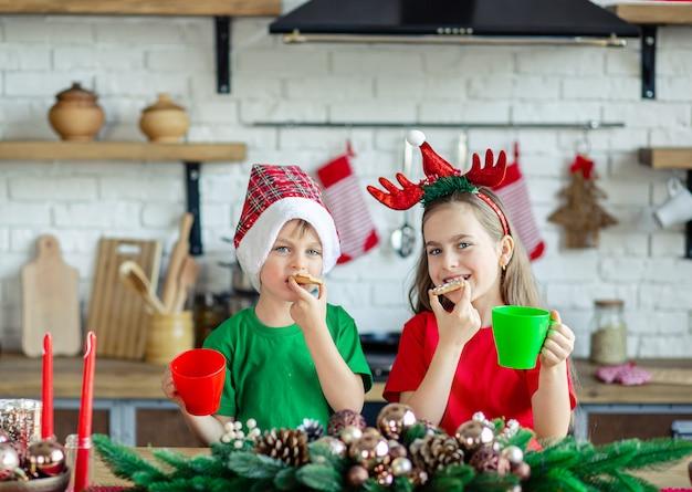 Goedemorgen. broer en zus drinken thee aan de keukentafel met koekjes in de keuken. een tijd van wonderen en vervulling van verlangens.