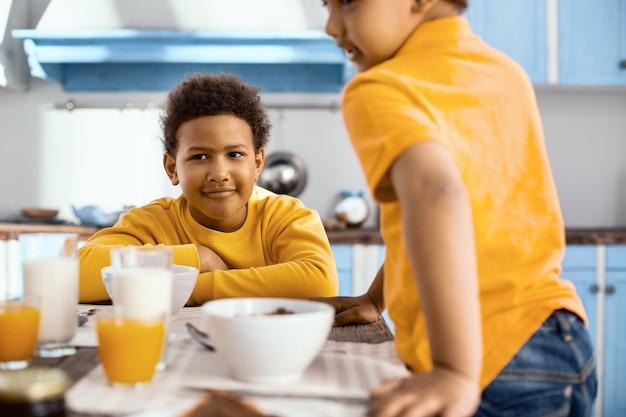 Goedemorgen. charmante pre-tienerjongen die aan tafel zit en ontbijten terwijl zijn jongere broer bij hem aan tafel zit