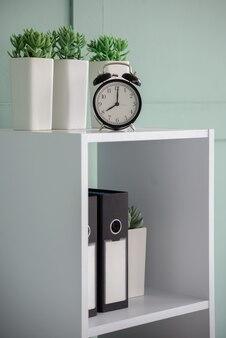 Goedemorgen concept moderne wekker en kamerplant op nachtkastje
