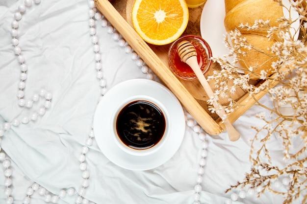Goedemorgen. continentaal ontbijt op witte lakens.