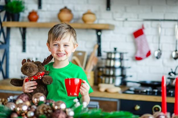 Goedemorgen. een kleine jongen drinkt thee aan de keukentafel en knuffelt een teddy-eland. een tijd van wonderen en vervulling van verlangens.