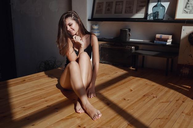 Goedemorgen, gelukkige en vreugdevolle ochtend. de zon schijnt in de slaapkamer, vrouw kijkt uit het raam zittend op de houten vloer