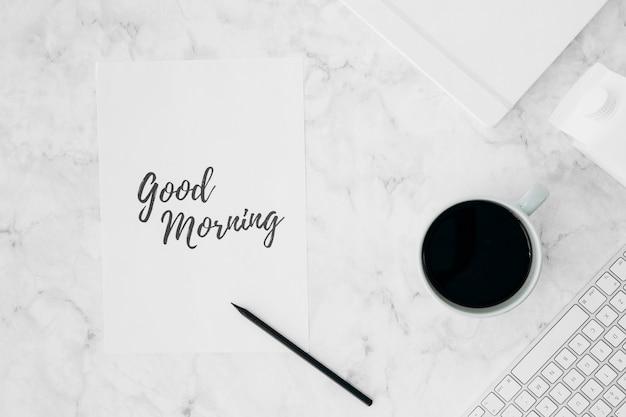 Goedemorgen geschreven op wit papier met potlood; koffiekop; dagboek; melkpak en toetsenbord op gestructureerd bureau