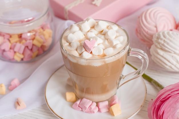 Goedemorgen kaart in roze. een kopje koffie, een marshmallow en een roze bloem op een lichte houten tafel.