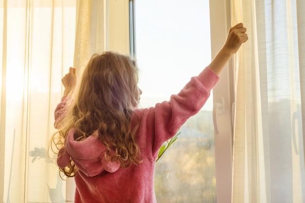 Goedemorgen. meisje kind in pyjama opent gordijnen