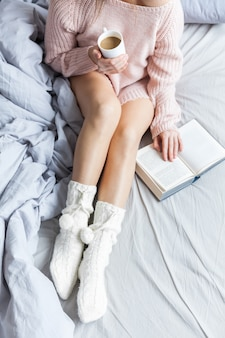 Goedemorgen met koffie. jonge vrouw in bed met kop