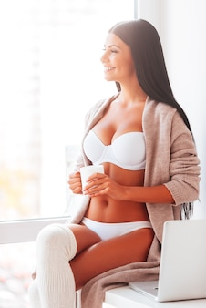 Goedemorgen. mooie jonge vrouw in lingerie en trui die koffie drinkt en thuis door een raam kijkt