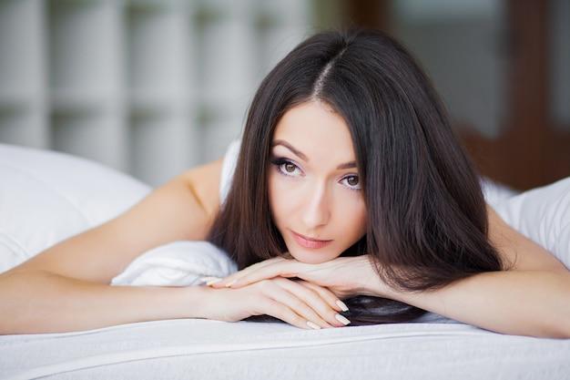 Goedemorgen. portret van een glimlachende vrij jonge donkerbruine vrouw die in wit bed ontspant
