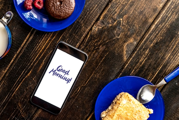 Goedemorgen tekst op telefoon eten ontbijt concept, met melk cake en fruit op houten tafel plat lag, f