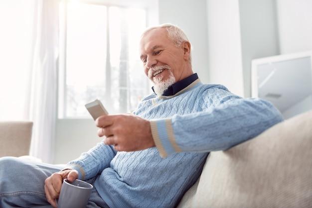 Goedemorgen. vrolijke oudere man die comfortabel op de bank zit en zijn kinderen sms't terwijl hij koffie drinkt, een brede glimlach op zijn gezicht