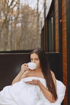 Goedemorgen. vrouw in een deken. dame zittend op terras. brunette drinkt een kop koffie.