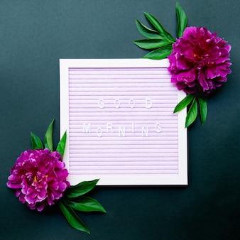 Goedemorgen zin op letterbord met roze pioenrozen