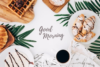 Goedemorgenbericht omringd met gebakken croissant; wafels; broodjes; tortilla's en koffie op witte achtergrond