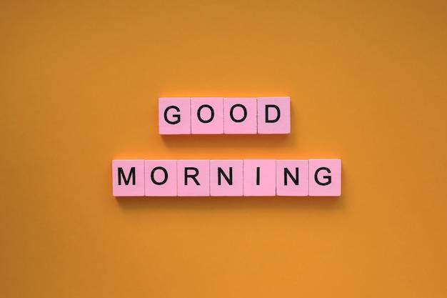 Goedemorgenwoorden op een oranje oppervlak