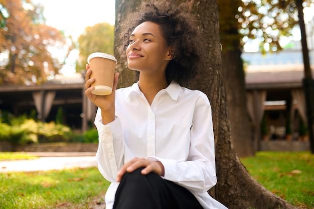 Goedendag. een schattige jonge vrouw die tijd doorbrengt in het park en er tevreden uitziet