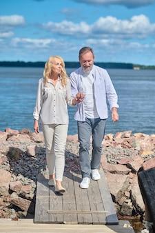 Goedendag. volwassen lachende bebaarde man en blonde vrouw die hand in hand lopen op de kust op zonnige dag