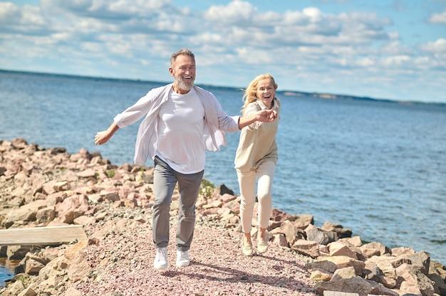 Goedendag. volwassen lachende bebaarde man en blonde vrouw die hand vasthouden aan de kust op mooie dag