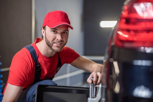 Goedendag, werk. gelukkig jonge bebaarde man in rode pet en t-shirt gehurkt in de buurt van autowiel in werkplaats werken