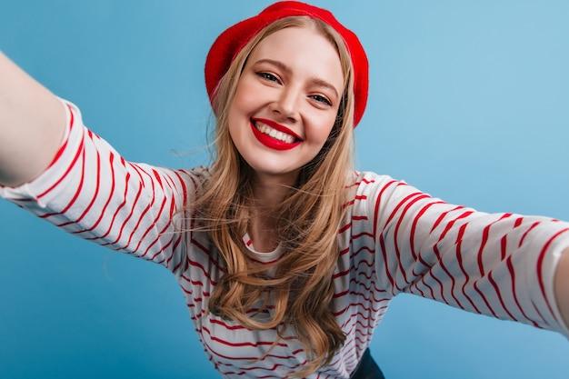 Goedgehumeurd frans meisje dat selfie met glimlach neemt. het gelukkige blonde vrouwelijke model stellen op blauwe muur.