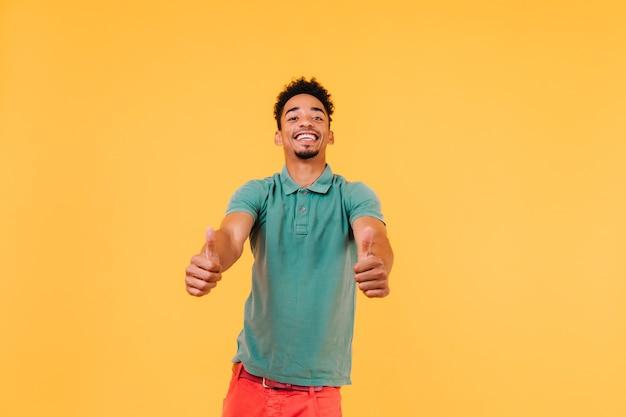 Goedgehumeurd lachende man poseren met duimen omhoog. blije stijlvolle man geïsoleerd.