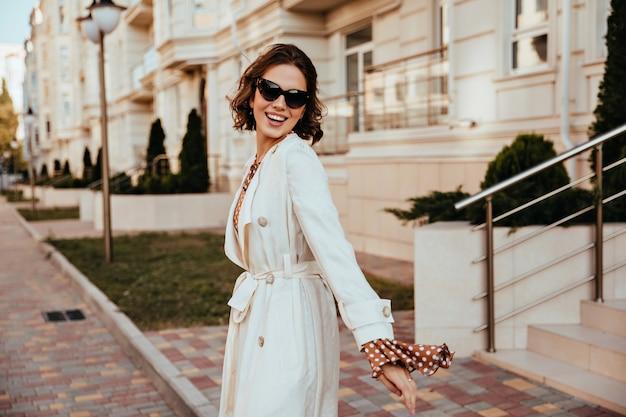 Goedgehumeurd meisje in lange jas lachend op straat. goed geklede europese vrouw tijd doorbrengen in de stad.