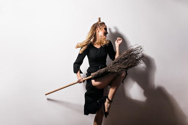 Goedgehumeurd meisje in zwarte outfit dansen met bezem in halloween. binnenfoto van blije blonde dame in carnavalskostuum die positieve emoties uitdrukt.