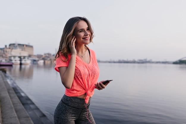 Goedgehumeurd meisje luistert muziek na de training. aantrekkelijke vrouwelijke atleet poseren in de buurt van rivier met glimlach.