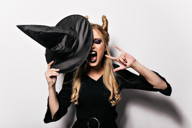 Goedgehumeurd meisje met blond haar dat van carnaval geniet. opgewonden dame halloween vieren in heksenkleding.