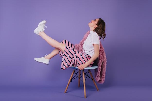 Goedgehumeurd meisje, zittend op een stoel en zwaaiende benen. lachende brunette dame in stijlvolle outfit.