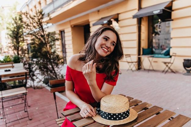 Goedgehumeurd vrouwelijk model dat in straatkoffie rust. openluchtportret van blij donkerbruin meisje dat met strohoed geluk uitdrukt.