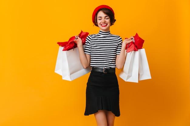 Goedgehumeurd vrouwelijk model poseren na het winkelen