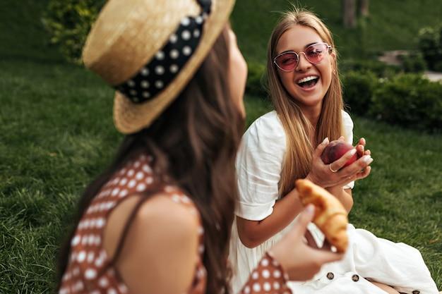 Goedgehumeurde blonde gebruinde dame in stijlvolle rode zonnebril en witte jurk lacht, praat met haar vriend en houdt appel vast