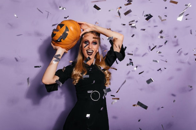 Goedgehumeurde heks die zich op halloween voorbereidt. gelukkig blonde vampier dansen op feestje.