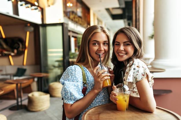 Goedgehumeurde jonge blonde en brunette vrouwen in trendy bloemenblouses glimlachen oprecht, drinken limonade en rusten in het straatrestaurant