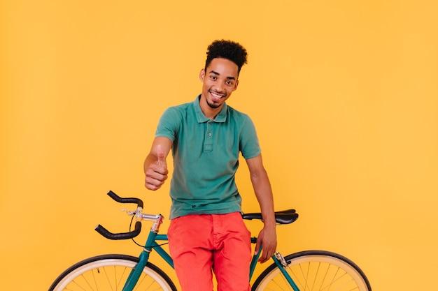 Goedgehumeurde mannelijke wielrenner poseren met duim omhoog. portret van blij brunette man poseren met fiets.