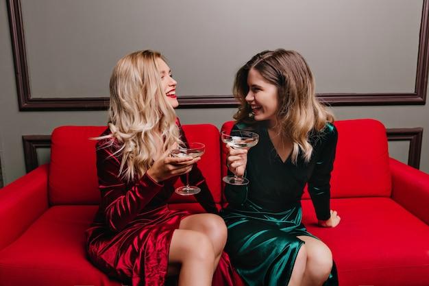 Goedgehumeurde meisjes die wijn drinken en praten. binnenfoto van tevreden dames die op rode laag met wijnglazen zitten.