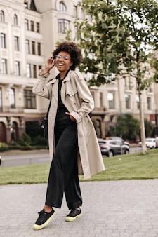 Goedgehumeurde mooie brunette krullende vrouw in zwarte oversized broek, beige trenchcoat en bril glimlacht en poseert buiten