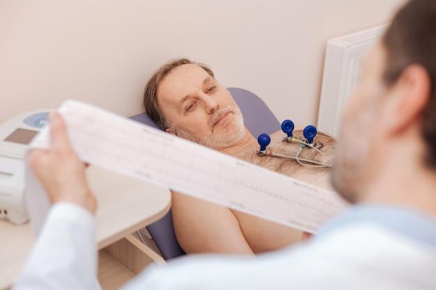 Goedgehumeurde volwassen man die wacht op wat zijn dokter hem zegt terwijl hij de laatste tests voltooit na zijn behandeling