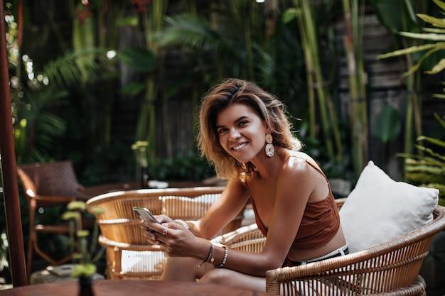 Goedgehumeurde vrouw in bruine bijgesneden top glimlacht oprecht en houdt mobiel vast