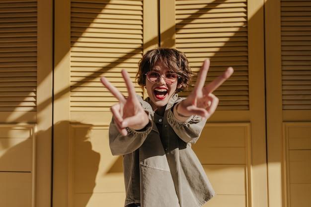 Goedgehumeurde vrouw met rode lippen die vredesteken op gele deuren tonen. koele dame met krullend haar in glazen glimlacht op gele deuren