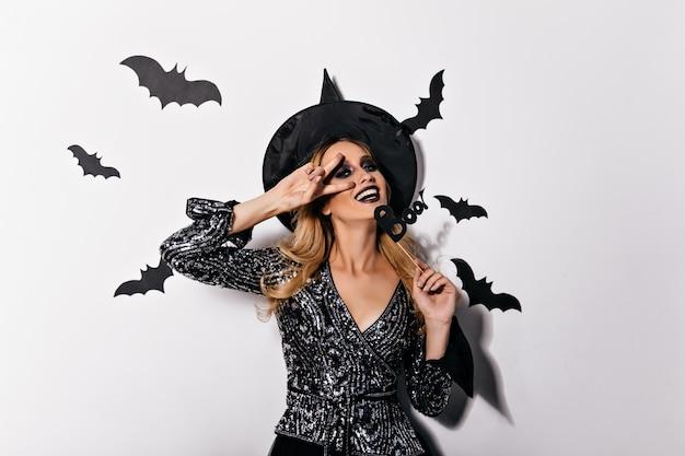 Goedgehumeurde vrouwelijke tovenaar die positieve emoties in halloween uitdrukt. foto van lachende positieve heks met blond haar.