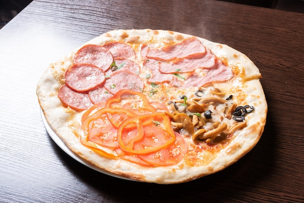 Goedkope pizza 4 seizoenen. met ham, pepperoni, champignons en tomaten. voor welk doel dan ook.