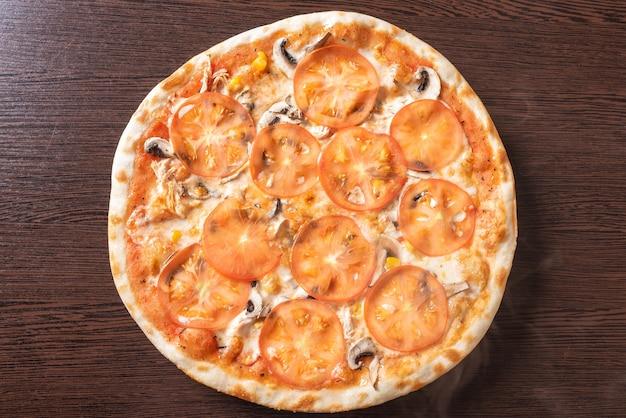 Goedkope pizza met champignons, tomaten en maïs. voor elk doel.