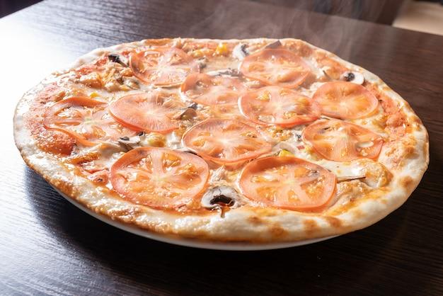 Goedkope pizza met champignons, tomaten en maïs. voor welk doel dan ook.